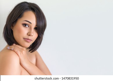 Beautiful young woman portrait in front of white background wall. Beauty shot of lady with perfect face skin.