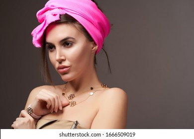 Beautiful young woman portrait with silk scarf on her head, gray background with copy space