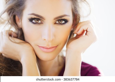 Beautiful young woman portrait with smoky eyes makeup and long hair posing in daylight.