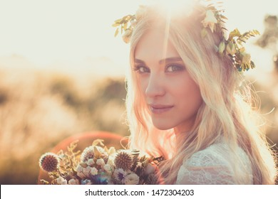 Beautiful young woman portrait in a white dress in boho style with a floral wreath in the summer in the field. Selective soft focus.