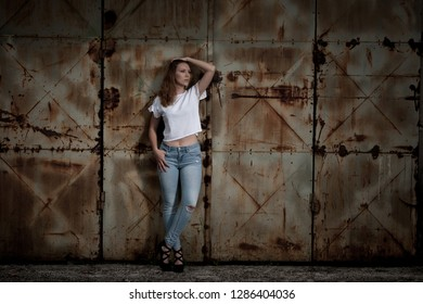 Beautiful young woman pose near rusty industrial dor in urban environment