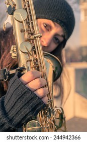 Beautiful young woman posing in the city streets with her saxophone