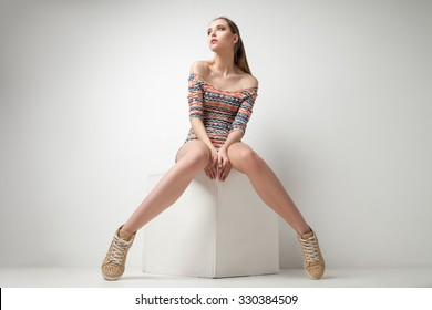 Beautiful young woman posing in dress on cube at studio