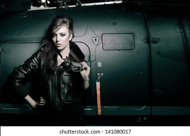Beautiful young woman posing fashion in airport shed with pilot glasses