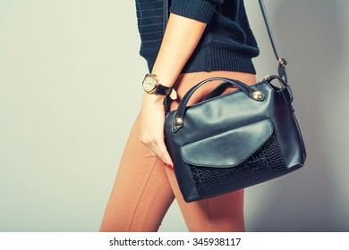 Beautiful young woman posing with handbag and copy space. Vintage color tone.