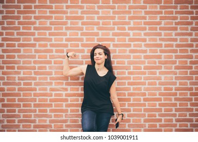 Beautiful young woman posing leaning against brick wall looking camera holding smart phone - positive emotions, positive feelings, technology concept
