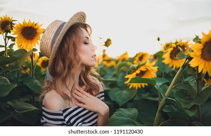beautiful young woman posing near sun flowers. summer portrait at the field. girl with straw hat. Happy woman in beauty field with sunflowers. Sunflare, sunbeams, glow sun. curly blonde woman