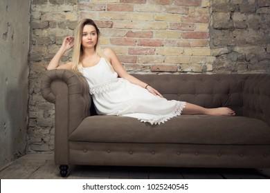 Beautiful young woman posing on sofa