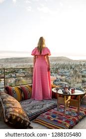 Beautiful young woman posing on ruff in  luxury dress