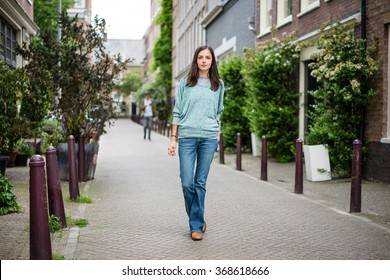beautiful young woman posing on Amsterdam 's streets with a biscuit in hand dressed casual