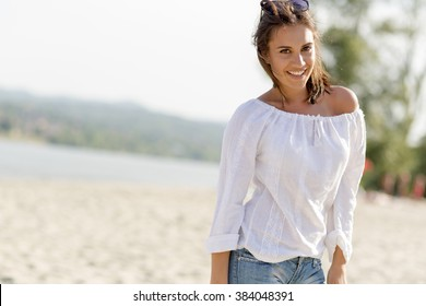 Beautiful young woman posing on a windy summer day on the beach