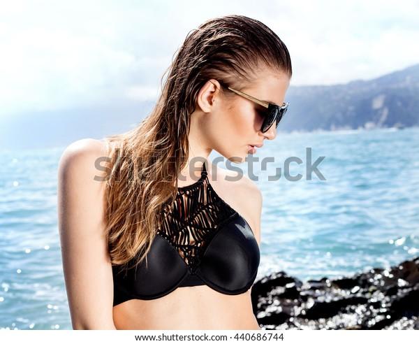 Beautiful young woman posing on the rocky beach, summer photo. Girl wearing black bikini.