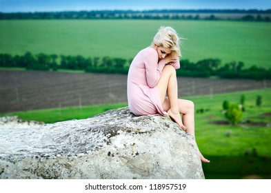 Beautiful young woman posing over picturesque landscape.