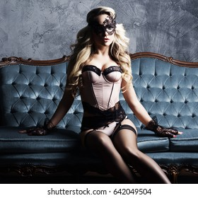 Beautiful and young woman posing in sexy lingerie and Venetian mask on blue sofa. Vintage interior and retro background.