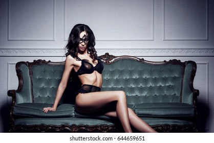 Beautiful and young woman posing in sexy lingerie and Venetian mask on cyan sofa. Vintage interior and retro background.