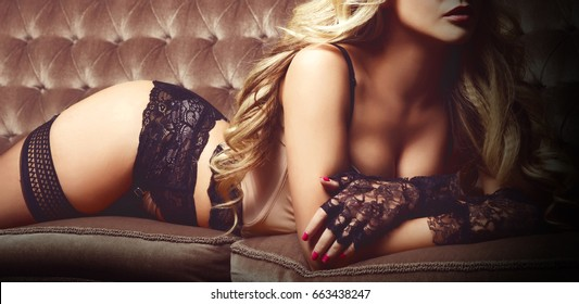 Beautiful and young woman posing in sexy lingerie and Venetian mask on brown sofa. Vintage interior and retro background.