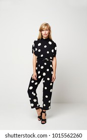 Beautiful young woman posing in spotted jumpsuit, portrait
