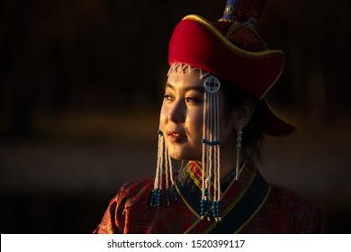 Beautiful young woman posing in traditional Mongolian dress in sunset light. Ulaanbaatar, Mongolia.