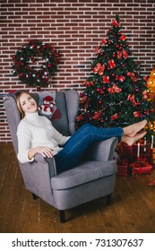 Beautiful young woman posing under Christmas tree in a holiday interior