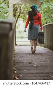 Beautiful young woman posing in vintage 1940s clothes, on a bridge, focussing on legs