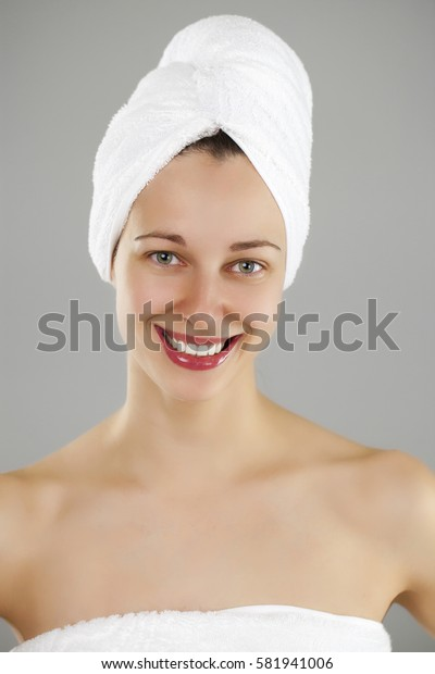 Beautiful young woman posing in white towel. Spa, healthcare. isolated on grey background