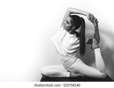 Beautiful young woman posing in yoga asana. Relax and active lifestyle. Black and white photo shot.