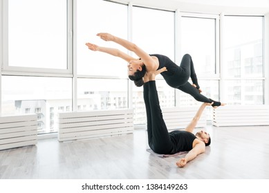 Beautiful young  woman practice acro yoga exercise with man partner  in white fitness studio with big windows on background
