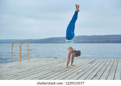 Beautiful young woman practices handstand yoga asana Adho Mukha Vrikshasana - Downward facing Tree pose on the wooden deck near the lake