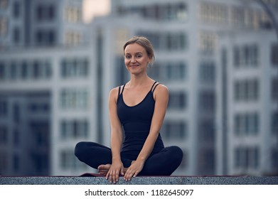 Beautiful young woman practices yoga asana Sukhasana - The Easy Sitting crosslegged Pose outdoors against the background of a modern city
