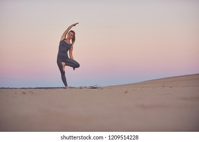 Beautiful young woman practices yoga asana Parshva Vrikshasana - Tree pose in the desert at sunset