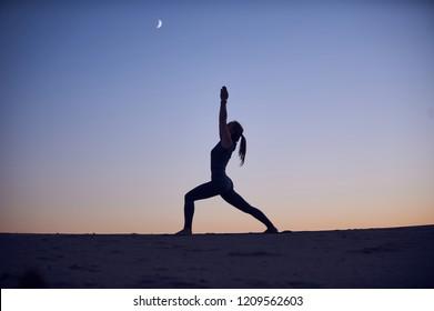 Beautiful young woman practices yoga asana Virabhadrasana 1 - warrior pose 1 in the desert at night