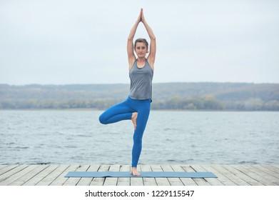 Beautiful young woman practices yoga asana Parshva Vrikshasana - Tree pose on the wooden deck near the lake
