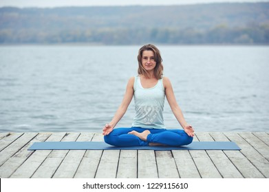 Beautiful young woman practices yoga asana Padmasana - Lotus pose on the wooden deck near the lake
