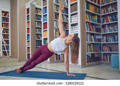 Beautiful young woman practices yoga asana Beautiful young woman practices yoga asana Vasishthasana - side plank pose in the library