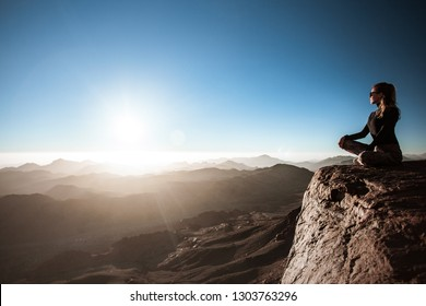 beautiful young woman practices yoga on Moses mountain at sunrise