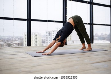 Beautiful young woman practices yoga asana Adho Mukha Svanasana - downward facing dog at the yoga class.