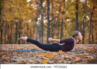 Beautiful young woman practices yoga asana Salabhasana locust pose on the wooden deck in the autumn park
