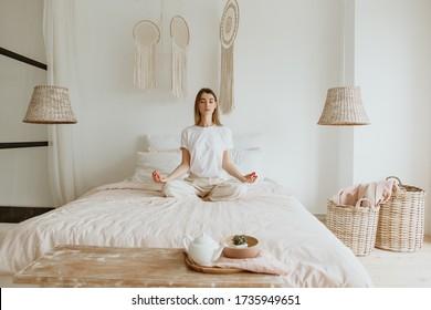 Schöne junge Frau, die Meditation auf dem Bett praktiziert.