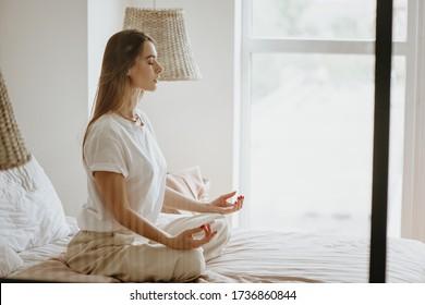 Schöne junge Frau, die Meditation auf dem Bett zu Hause praktiziert.