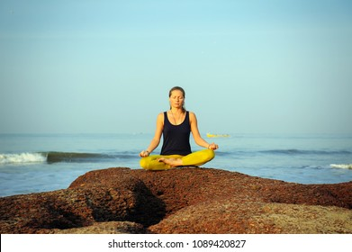 Beautiful young woman practicing yoga and stretching exercises at the summer tropic ocean  seashore