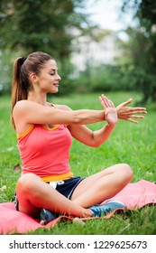 Beautiful young woman practicing yoga and stretching in city park on a sunny summer day. Active sport lifestyle in urban environment.