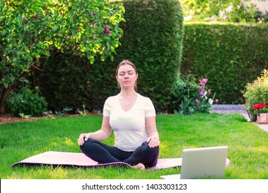 Beautiful young woman practicing yoga in garden outdoors following guide of online tutorial or trainer on laptop. Healthy lifestyle. Exercising at home. Meditation online.