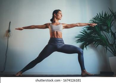 Hermosa joven practicando yoga en casa por la mañana, concepto de bienestar Estilo de vida saludable