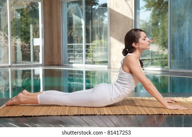 Beautiful young woman practicing yoga on mat
