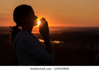 Beautiful young woman praying at sunset against the sky in summer