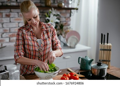 Beautiful young woman is preparing vegetable salad in the kitchen. Cooking At Home.