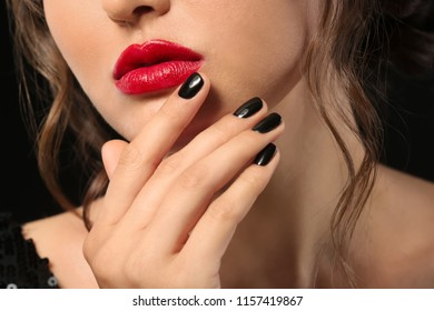 Beautiful young woman with professional manicure on black background, closeup