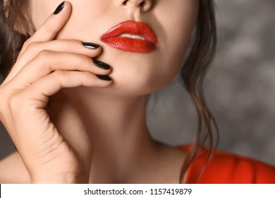 Beautiful young woman with professional manicure on dark grey background, closeup