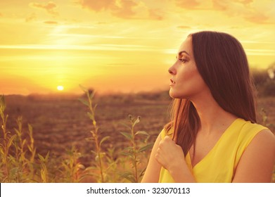 Beautiful young woman profile portrait against sunset autumn field, gazing into infinity