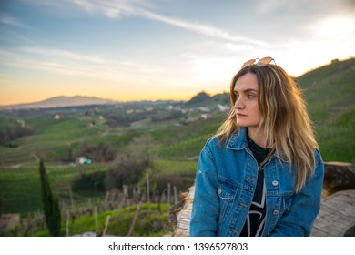 Beautiful young woman in the Prosecco's hills of Valdobbiadene taking picture or posing in a sunset light, in the green of the vineyards. Relax on a bench.